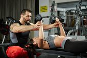 pic of personal trainer  - Personal fitness trainer assisting a young woman in the gym at a workout - JPG