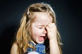image of cry  - Crying cute little girl with focus on her tears on dark background - JPG