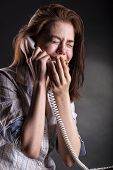 stock photo of crying  - Crying woman with a phone on a dark background - JPG