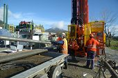 stock photo of  rig  - Drilling crewmen remove pipes from the drillstring on a rig drilling near Greymouth New Zealand - JPG