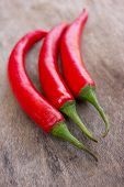 picture of red hot chilli peppers  - Hot red chili or chilli peppers over wooden background - JPG