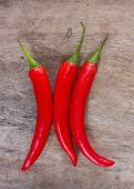 image of red hot chilli peppers  - Hot red chili or chilli peppers over wooden background - JPG