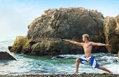 stock photo of virabhadrasana  - Young man doing yoga and meditating in warrior pose at sea beach - JPG