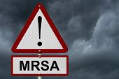 stock photo of mrsa  - MRSA Caution Sign Red and White Triangle Caution sign with word MRSA with stormy sky background - JPG