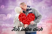 stock photo of girly  - Happy mature couple in winter clothes holding red heart against pink and purple girly design - JPG