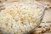 picture of popcorn  - This is a shot of a glass bowl full of hot air popped popcorn on a wooden table. Shot with a shallow depth of field.