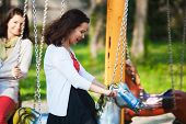 stock photo of memento  - Young women enjoying childhood play time while spinning in a carousel - JPG