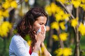 pic of hay fever  - Young woman blowing her nose while being in the nature - JPG