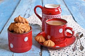 stock photo of milkman  - Small cone-shaped biscuits are brown in ceramic pot of red color on the background of mugs of cocoa and the milkman ** Note: Shallow depth of field - JPG