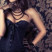 picture of corset  - woman wearing black corset and pearls against retro background - JPG