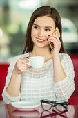 picture of pullovers  - Young beautiful girl in white pullover sitting in urban cafe with a cup of coffee and talking on smart phone - JPG