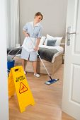 picture of maids  - Female Maid Cleaning Floor In Hotel Room - JPG