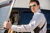 stock photo of guns  - Young confident businessman in sunglasses with gun coming out of his luxurious car - JPG