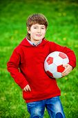 image of 7-year-old  - Cute 7 years old boy playing with a ball outdoor - JPG