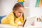 stock photo of pullovers  - Little pretty girl in yellow pullover touching digital tablet on colorful background - JPG