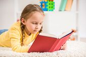 image of pullovers  - Little pretty girl in yellow pullover reading book on colorful background - JPG