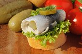 stock photo of baguette  - Baguette slice with sour herring pickled herring garnished with lettuce gerkin tomatoes and onion on a wooden board - JPG