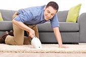 stock photo of carpet  - Young joyful man vacuuming a carpet with a handheld vacuum cleaner isolated on white background - JPG