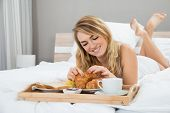 stock photo of bed breakfast  - Young Woman Lying On Bed Having Breakfast - JPG