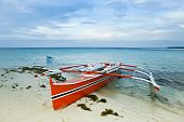 pic of camiguin  - traditional filipino banka outrigger fishing boat on white sand beach of camiguin island near mindanao in the philippines - JPG