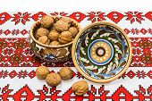 pic of ceramic bowl  - Two ceramic bowl with floral ornaments and walnuts on the tablecloth with a white background - JPG