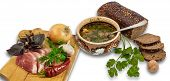 image of ceramic bowl  - Ceramic bowl of soup bread spoon and some of the ingredients for cooking  - JPG