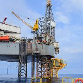 stock photo of offshore  - Offshore Jack Up Drilling Rig Over The Production Platform in The Middle of The Sea View from Crew Boat - JPG
