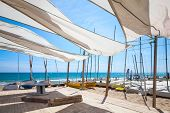 stock photo of sails  - Awnings in sails shape covering relax area near sailing boats on the sandy beach in Calafell town coast of Mediterranean sea Catalonia Spain - JPG