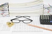 picture of spectacles  - Brown pencil with black spectacles and gold coins have pile of paperwork as background - JPG