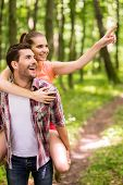 foto of walking away  - Happy young loving couple walking in park while woman hugging man and pointing away with smile - JPG