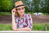 stock photo of toothless smile  - Beautiful young woman adjusting her cowboy hat and smiling while standing on ranch with horse walking in the background - JPG