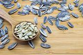 foto of edible  - Edible Sunflower seeds in wood spoon on wood background - JPG