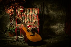 picture of edwardian  - A vintage acoustic guitar leans against an empty antique patterned armchair - JPG