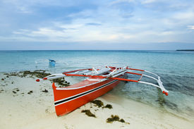 picture of camiguin  - traditional filipino banka outrigger fishing boat on white sand beach of camiguin island near mindanao in the philippines - JPG