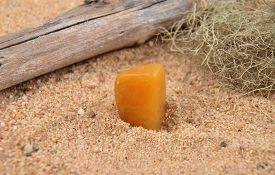 foto of calcite  - Colorful and crisp image of orange calcite on beach - JPG