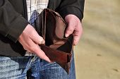 stock photo of amortization  - Man is looking for money in the empty wallet - JPG
