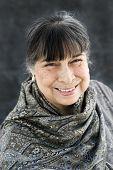 foto of senora  - portrait of a hispanic grandmother in a grey scarf smiling - JPG