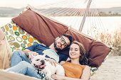 Hipster Couple On A Trip To The Beach, Young Freelancer Man Relaxing In A Hammock With His Woman, Ro poster