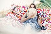 Beautiful Hipster Girl In Stylish Dress Hiding Behind Hat And Smiling While Resting On A Hammock On poster