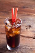 Close Up On A Cold Refreshing Soft Drink With Ice On A Dark Wooden Background poster