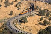 stock photo of bnsf  - Diesel electric locomotives drag their train up Tehachapi Mountain California - JPG