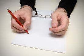 pic of hackney  - handcuffed  man  writing  a confession of the crime - JPG