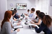 Group Of Businesspeople Having Video Conference With Another Business Team In Office poster