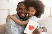 African Dad Embracing Daughter Holding Greeting Card On Fathers Day poster