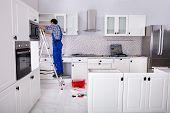 Rear View Of A Man Standing On Ladder Adjusting Cabinet Door Hinge On Kitchen Cabinet poster