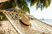Close-up Of Sun Hat On Hammock Over The Sand At Beach poster
