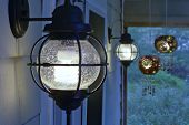 foto of screen-porch  - Pair of exterior compact fluorescent electric light fixtures on screened porch - JPG