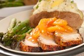 Cooked Pork With A Peach Sauce, Baked Potato And Asparagus poster