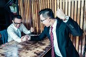 Two Businessman Expressed A Serious Expression And Fighting By Used Arm Wrestling On Wood Table. One poster