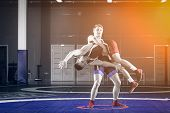 Two Young Men In Blue And Red Wrestling Tights Are Wrestlng And Making A Suplex Wrestling On A Yello poster
